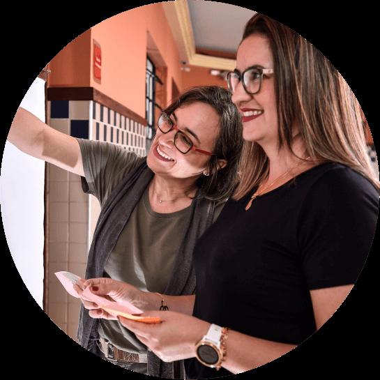 Duas mulheres sorrindo, uma apontando para frente e a outra com um papel na mão