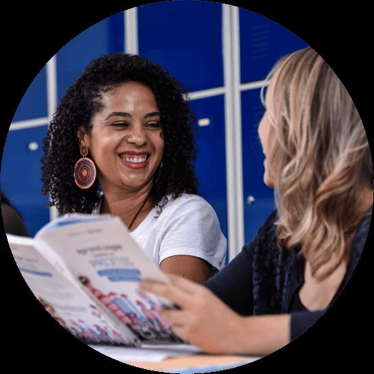 Duas mulheres sorriem se olhando com um livro na mão em uma mesa